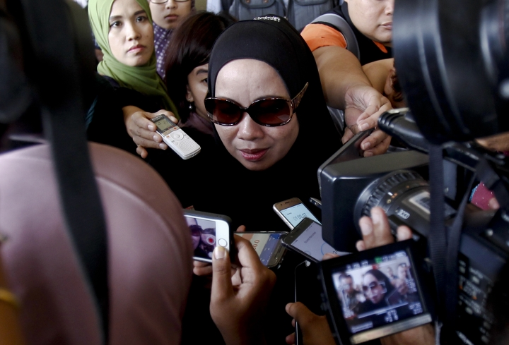 Mother of the fire victim Hartini Abdul Ghani, center, speaks to journalists during the court hearing at a court house in Kuala Lumpur, Malaysia Thursday, Sept. 28, 2017. Two Malaysian teenagers have been charged with murder after being accused of intentionally setting a fire at an Islamic boarding school that killed 23 people, mostly students. (AP Photo/Daniel Chan)