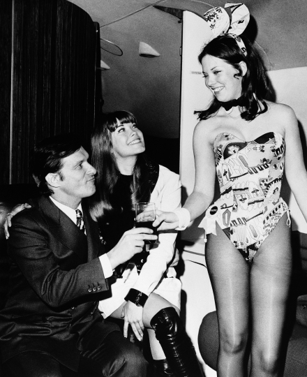 FILE - In this March 1970 file photo, Hugh Hefner, left, and girlfriend Barbi Benton, center, are served by Playboy Club Bunny Cheri upon their arrival at La Guardia aboard the Big Bunny, Heffner's jet, in New York. Playboy magazine founder and sexual revolution symbol Hefner has died at age 91. The magazine released a statement saying Hefner died at his home in Los Angeles of natural causes on Wednesday night, Sept. 27, 2017, surrounded by family .(AP Photo, File)