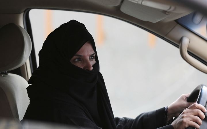 FILE- In this Saturday March 29, 2014 file photo, a woman drives a car on a highway in Riyadh, Saudi Arabia, as part of a campaign to defy Saudi Arabia's ban on women driving. Saudi Arabia authorities announced Tuesday Sept. 26, 2017, that women will be allowed to drive for the first time in the ultra-conservative kingdom from next summer, fulfilling a key demand of women's rights activists who faced detention for defying the ban. (AP Photo/Hasan Jamali, FILE)