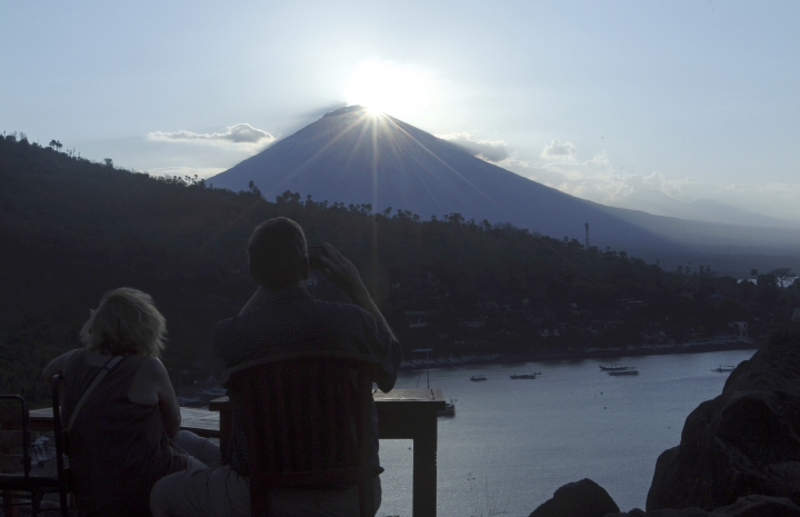 Foreigner tourists watch the sunset over the Mount Agung volcano in Karangasem, Bali, Indonesia, Thursday, Sept. 28, 2017. More than 120,000 people have fled the region around the Mount Agung volcano on the Indonesian tourist island of Bali, fearing it will soon erupt, an official said Thursday. (AP Photo/Firdia Lisnawati)
