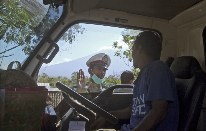 A police officer warns a truck driver heading towards the volcano danger zone as Mount Agung volcano is seen in the background in Karangasem, Bali, Indonesia, Thursday, Sept. 28, 2017. Warnings that the volcano on the tourist island will erupt have sparked an exodus as authorities have ordered the evacuation of villagers living within a high danger zone that in places extends 12 kilometers (7.5 miles) from its crater. (AP Photo/Firdia Lisnawati)