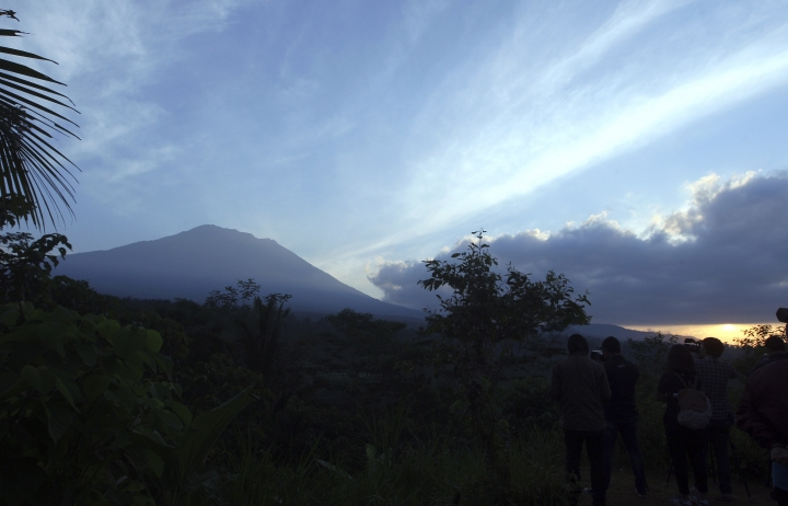 Mount Agung is seen at sunrise from an observation point which is about 12 kilometer (7.4 miles) away from the volcano in Karangasem, Bali, Indonesia, Thursday, Sept. 28, 2017. The exodus from the menacing volcano on the Indonesian tourist island is nearing 100,000 people, a disaster official said Wednesday, as hundreds of tremors from the mountain are recorded daily. (AP Photo/Firdia Lisnawati)