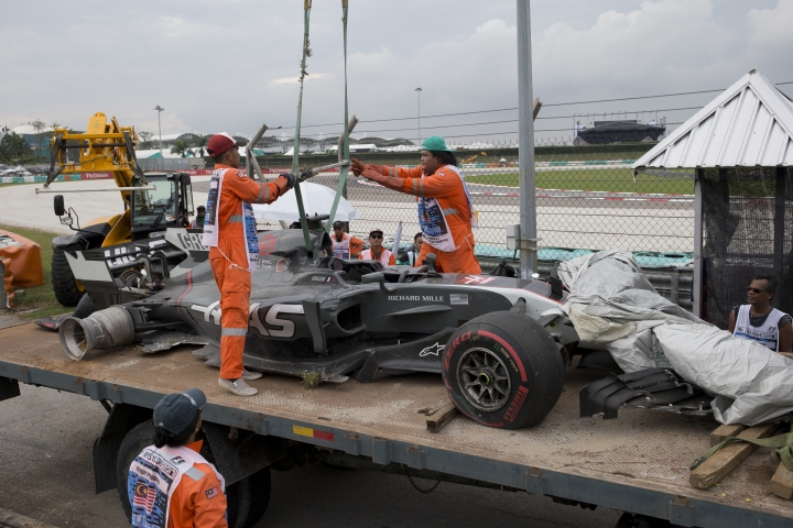 Track crew lifts the car of Haas driver Romain Grosjean of France after it crashed out on Turn 14 during the second practice for the Malaysian Formula One Grand Prix in Sepang, Malaysia, Friday, Sept. 29, 2017. (AP Photo/Thomas Lam)