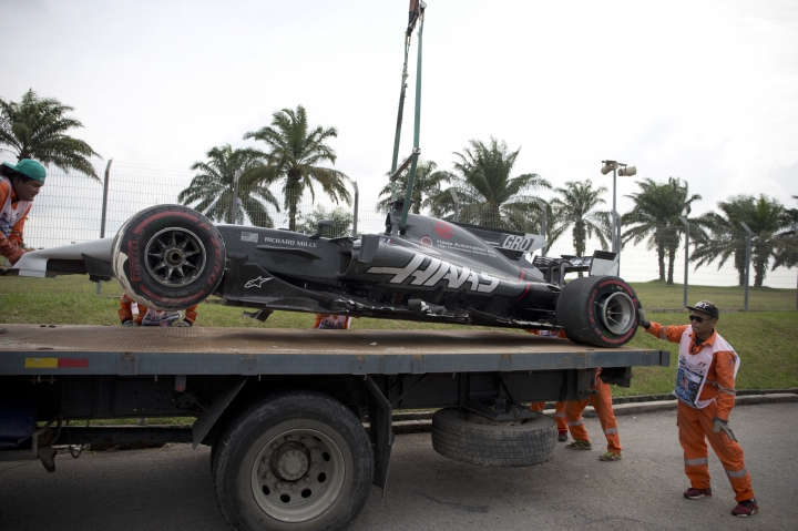 Track crew lifting Haas driver Romain Grosjean of France car after it crashed out on Turn 14 during the second practice at the Sepang International Circuit for the first practice session for the Malaysian Formula One Grand Prix in Sepang, Malaysia, Friday, Sept. 29, 2017. (AP Photo/Thomas Lam)