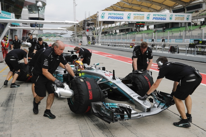 Crew push Mercedes driver Lewis Hamilton of Britain's car in to the garage from pit lane during the second practice at the Sepang International Circuit for the first practice session for the Malaysian Formula One Grand Prix in Sepang, Malaysia, Friday, Sept. 29, 2017. (AP Photo/Vincent Thian)