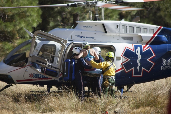 In this Wednesday, Sept. 27, 2017, photo provided by Dakota Snider, photographer and Yosemite resident, a woman is carried into a helicopter after being rescued off El Capitan following a major rock fall in Yosemite National Park, Calif. All areas in California's Yosemite Valley are open Thursday, a day after the fatal rock fall. (Dakota Snider via AP)