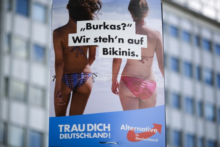 """FILE - In this Aug. 13, 2017 file photo an election campaign poster of the German nationalist anti-migrant party AfD, Alternative for Germany, reading """"Burkas? We like bikinis."""" is displayed in Berlin. The sentence at the bottom reads: 'Trust yourself Germany'. A law prohibiting any kind of full face covering but known popularly as the """"Burqa Ban,"""" takes effect in Austria Sunday, Oct. 1, 2017. (AP Photo/Markus Schreiber,file)"""