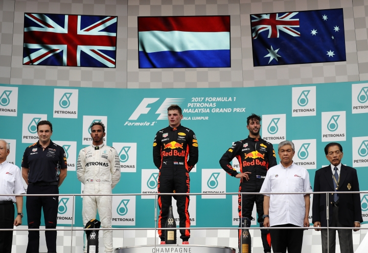 Race winner Red Bull driver Max Verstappen, centre, of the Netherlands stands on the podium with second placed Mercedes driver Lewis Hamilton of Britain and third placed Red Bull driver Daniel Ricciardo of Australia at the Malaysian Formula One Grand Prix at the Sepang International Circuit in Sepang, Malaysia, Sunday, Oct. 1, 2017. (AP Photo/Vincent Thian)