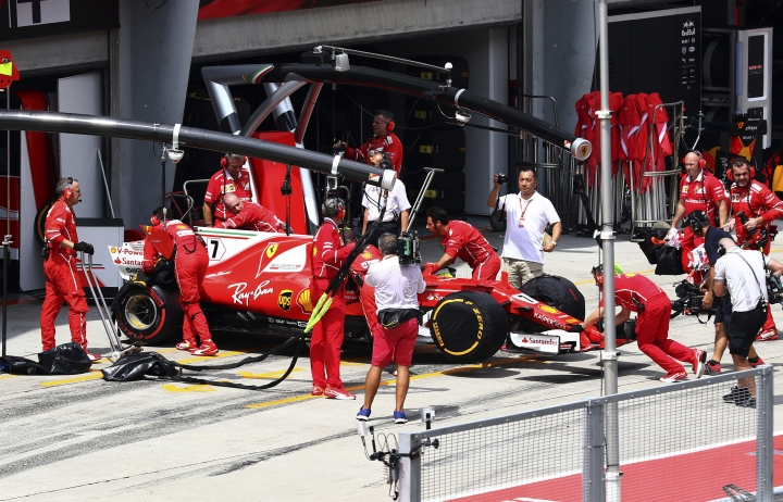 Mechanics for Ferrari driver Kimi Raikkonen of Finland push his car back into the team garage after he withdrew with mechanical failure prior to the start of the Malaysian Formula One Grand Prix at the Sepang International Circuit in Sepang, Malaysia, Sunday, Oct. 1, 2017. (AP Photo/Vincent Phoon)