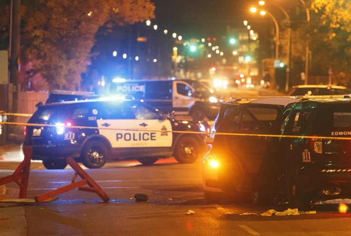 Police investigate the scene where a car crashed into a roadblock in Edmonton Alta, on Saturday, Sept. 30, 2017. Police say a vehicle rammed a traffic control barricade and sent an officer flying into the air 15 feet. (Jason Franson/The Canadian Press via AP)