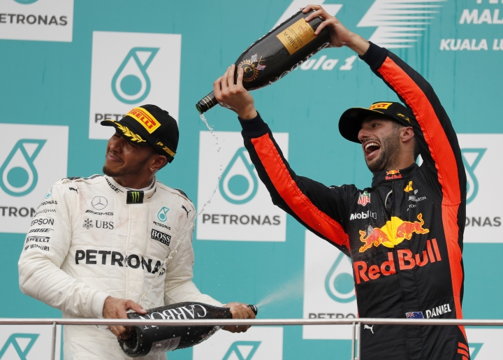 Third placed Red Bull driver Daniel Ricciardo, right, of Australia pours champagne on second placed Mercedes driver Lewis Hamilton of Britain on the podium at the Malaysian Formula One Grand Prix at the Sepang International Circuit in Sepang, Malaysia, Sunday, Oct. 1, 2017. (AP Photo/Vincent Thian)