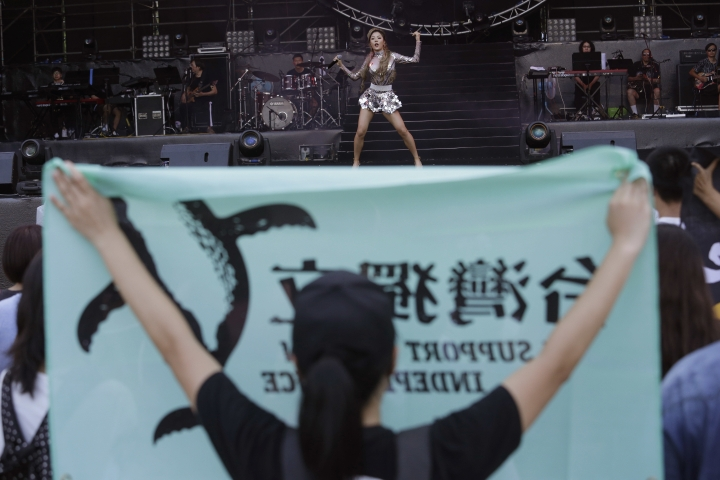 In this Sept. 24, 2017 photo, mainland Chinese singer Li Wa sings on stage as a Taiwanese pro-independence protester holds up a banner calling for Taiwan Independence during a Chinese-organized concert at the National Taiwan University in Taipei, Taiwan. Taiwanese police are looking for a final suspect involved in clashes at the Chinese-organized concert in Taipei between Taiwanese pro-independence protesters and Beijing supporters that's revealed divisions over China's influence on the self-ruled island. (AP Photo)