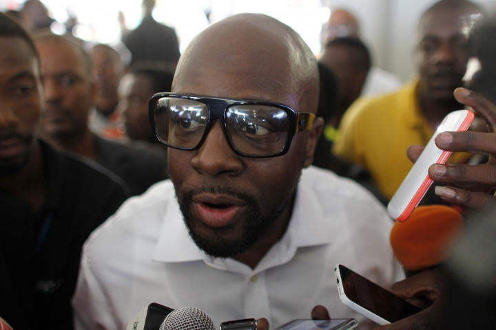 FILE - In this Nov. 20, 2016 file photo, Haitian-American musician Wyclef Jean talks to the press upon arrival to vote during elections in the Petion-Ville suburb of Port-au-Prince, Haiti. Jean, a three-time Grammy winner, gave the command for drivers to start their engines at a NASCAR race at Dover International Speedway in Delaware, Sunday, Oct. 1, 2017. (AP Photo/Ricardo Arduengo, File)