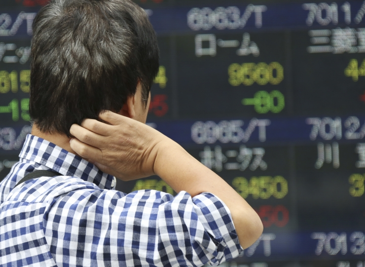 A man looks at an electronic stock board of a securities firm in Tokyo, Monday, Oct. 2, 2017. Shares in Asia are higher after China and Japan reported stronger than expected factory data. Many markets in the region were closed Monday for national holidays. (AP Photo/Koji Sasahara)