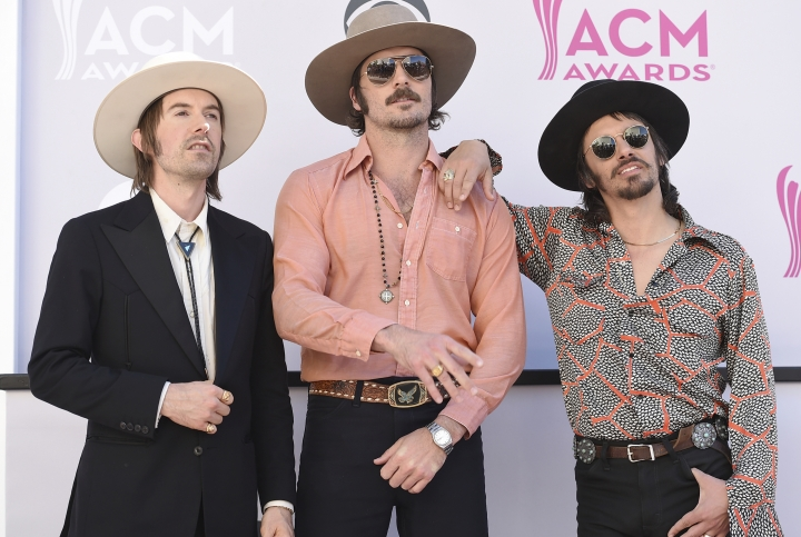 FILE - In this April 2, 2017 file photo, Jess Carson, from left, Mark Wystrach, and Cameron Duddy, of the musical group Midland, arrive at the 52nd annual Academy of Country Music Awards in Las Vegas. The trio said they have been inspired by all eras of music, from Nirvana and Paul Simon to Hank Williams Sr. and Otis Redding. Wystrach, the lead singer, said they wanted to write songs that stood the test of time and weren't disposable. (Photo by Jordan Strauss/Invision/AP, File)
