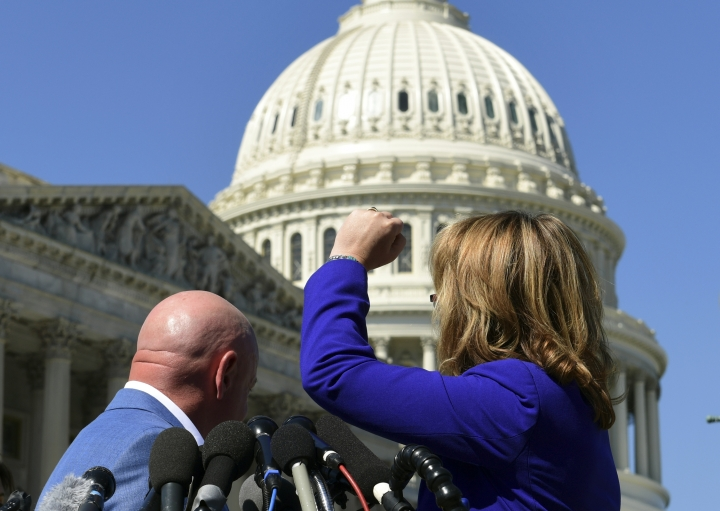 """Former Rep. Gabrielle Giffords, D-Ariz., right, shakes her fist at the United States Capitol as she and her husband Mark Kelly, left, speak on Capitol Hill in Washington, Monday, Oct. 2, 2017, about the mass shooting in Las Vegas. Giffords raised her fist at the Capitol and said """"the nation is counting on you"""" after the deadly mass shooting in Las Vegas. (AP Photo/Susan Walsh)"""