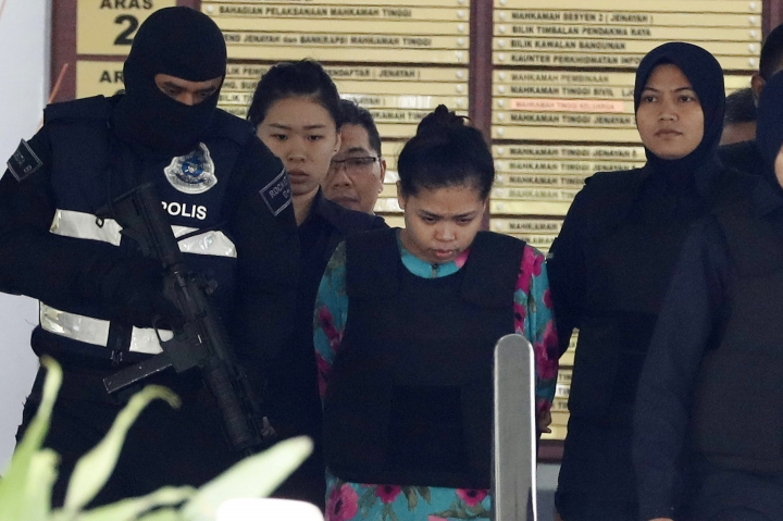 Siti Aisyah of Indonesia, center, is escorted by police as she leaves the court house in Shah Alam, Malaysia, Tuesday, Oct. 3, 2017. Aisyah and Doan Thi Huong of Vietnam pleaded not guilty as their trial opened Monday in the killing of Kim, widely thought to have been orchestrated by his half brother, North Korea's third-generation leader Kim Jong Un. (AP Photo/Vincent Thian)