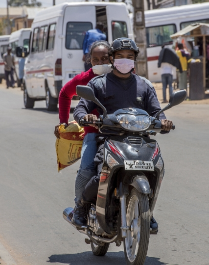 A motorcyclist and passenger wear face masks on a road in Antananarivo, Madagascar, Tuesday, Oct. 3, 2017. Authorities in Madagascar are struggling to contain an outbreak of plague that has killed at least two dozen people, and the government has begun a campaign to disinfect school classrooms in the city.(AP Photo/Alexander JOE)