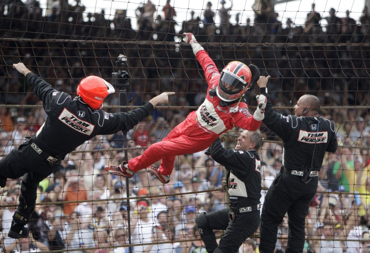 FILE - In this May 24, 2009, file photo, Helio Castroneves of Brazil climbs the safety fence with members of his pit crew after winning the Indianapolis 500 auto race at Indianapolis Motor Speedway in Indianapolis. Three-time Indianapolis 500 winner Helio Castroneves will move to Team Penske's sports car program next season, bringing his 20-year full-time IndyCar career to an end. Castroneves will still drive for Penske at the Indianapolis 500. (AP Photo/Jeff Roberson, File)