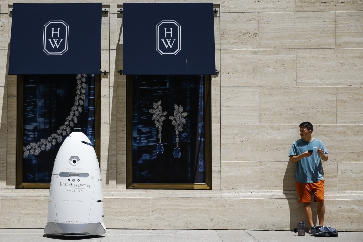 "FILE - In this Friday, Aug. 18, 2017, file photo, a new security robot, nicknamed ROD2, drives toward Daniel Webb as it patrols the sidewalks and parking garage at River Oaks District in Houston. The robot recently became the latest addition to a patrol team eager to experiment with fast-evolving technology. According to a survey by the Pew Research Center, three-quarters of Americans say it is at least ""somewhat realistic"" that robots and computers will eventually perform most of the jobs currently done by people. Roughly the same proportion worry that such an outcome will have negative consequences, such as worsening inequality. (Michael Ciaglo/Houston Chronicle via AP, File)"