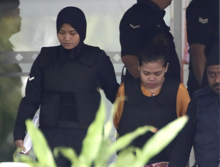 Indonesian Siti Aisyah, right, is escorted by police as she leaves after the court hearing at Shah Alam court house in Shah Alam, outside Kuala Lumpur, Wednesday, Oct. 4, 2017, in Malaysia. A judge and court officials wore face masks and surgical gloves in court as samples were admitted as evidence of where VX nerve agent was found on the body and clothing of estranged North Korean scion Kim Jong Nam. On the third day of the murder trial of the two suspects, a pathologist said VX was detected in Kim's eye mucus, on his face, in his blood and on his clothing.(AP Photo/Sadiq Asyraf)