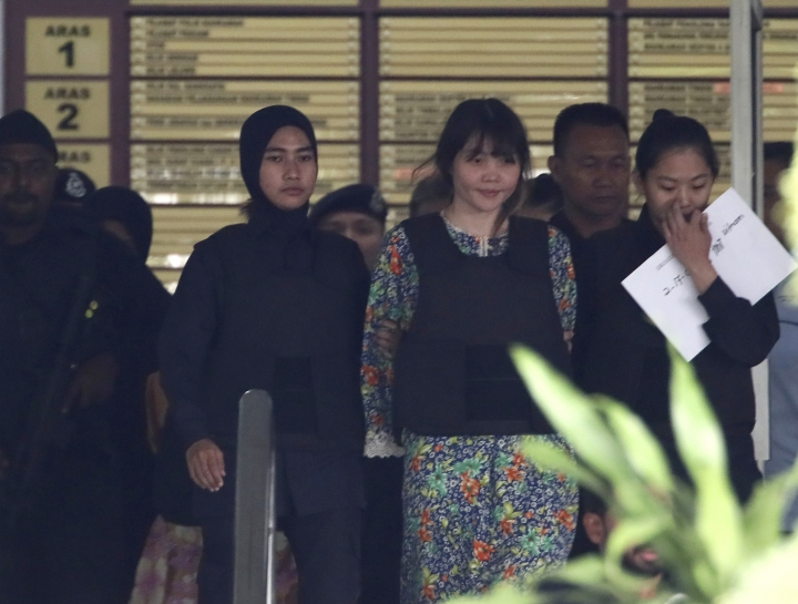Vietnamese Doan Thi Huong, center, is escorted by police as she leaves after the court hearing at Shah Alam court house in Shah Alam, outside Kuala Lumpur, Wednesday, Oct. 4, 2017, in Malaysia. A judge and court officials wore face masks and surgical gloves in court as samples were admitted as evidence of where VX nerve agent was found on the body and clothing of estranged North Korean scion Kim Jong Nam. On the third day of the murder trial of the two suspects, a pathologist said VX was detected in Kim's eye mucus, on his face, in his blood and on his clothing.(AP Photo/Sadiq Asyraf)
