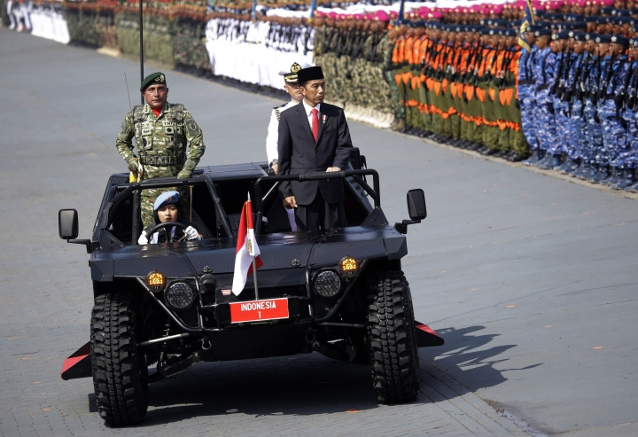 Indonesian President Joko Widodo, center, inspect the troops during a parade marking the 72nd anniversary of the Indonesian Armed Forces in Cilegon, Banten, Indonesia, Thursday, Oct. 5, 2017. Widodo has urged the military to stay out of politics and remain loyal to the government in an apparent rebuke to a series of outlandish statements from the country's top general. (AP Photo/Tatan Syuflana)