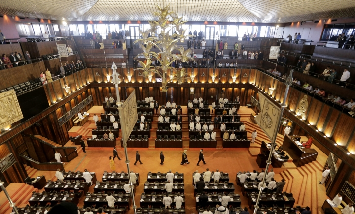 In this Tuesday, Oct. 3, 2017, photo, speaker of the Sri Lankan parliament Karu Jayasuriya, second rightncenter, arrives as lawmakers stand at the beginning of the sittings held to mark the country's seventieth anniversary of parliamentary democracy in Colombo, Sri Lanka. As lawmakers in Sri Lanka celebrate the 70th anniversary of the country's parliamentary democracy, one of the oldest in Asia, minorities including Tamils, Christians and Muslims remain on the fringes of society. (AP Photo/Eranga Jayawardena)