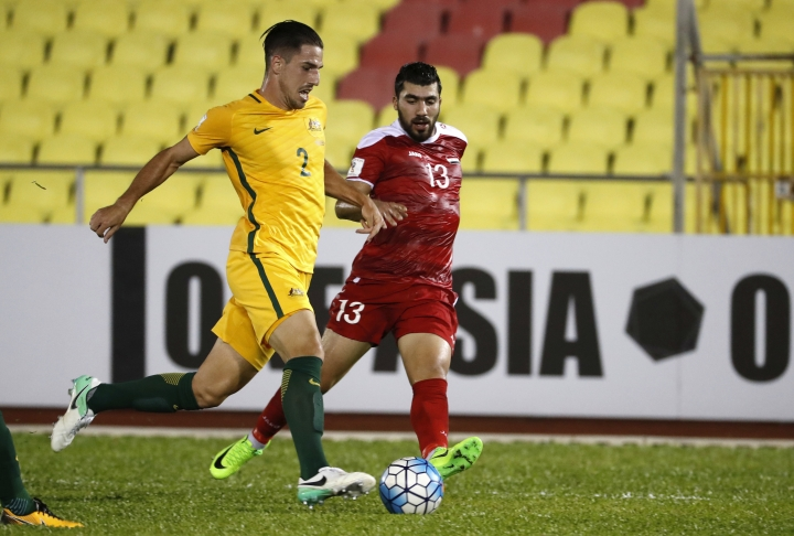 Australia's Milos Degenek, left, fight for control of the ball with Syria's Yousef Kalfa during the 2018 World Cup qualifying football match between Syria and Australia at the Hang Jebat Stadium in Melaka, Malaysia, Thursday, Oct. 5, 2017. (AP Photo/Vincent Thian)