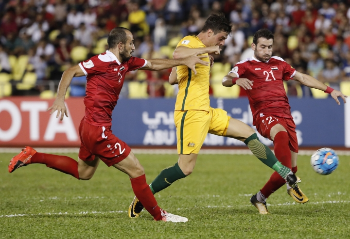 Australia's Tomi Juric, center, fight for control of the ball with Syria's Hadi Almasri, left, and Fahad Yousef during the 2018 World Cup qualifying football match between Syria and Australia at the Hang Jebat Stadium in Melaka, Malaysia, Thursday, Oct. 5, 2017. (AP Photo/Vincent Thian)