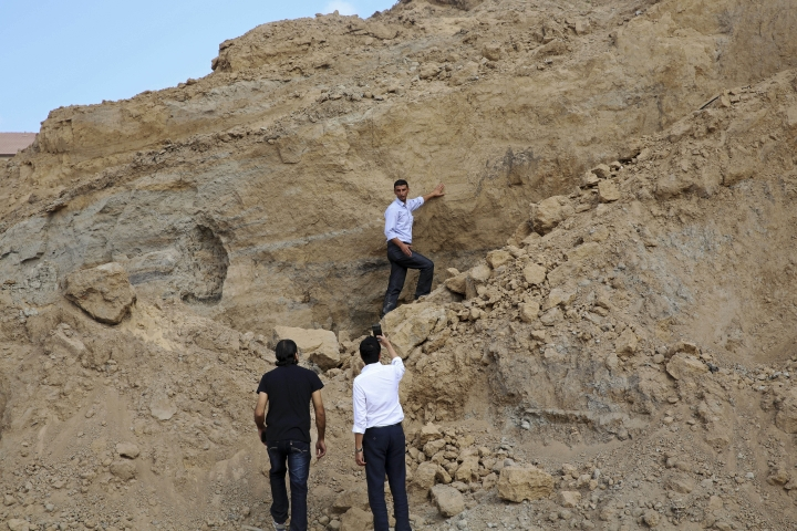 In this Tuesday, Sept. 26, 2017 photo, Junaid Sorosh-Wali, a UNESCO official, takes photos while Fadel al-A'utul, a worker with French excavation mission, explains to him the damage at Tel Es-Sakan hill, south of Gaza City. Palestinian and French archaeologists began excavating Gaza's earliest archaeological site nearly 20 years ago; unearthing what they believe is a rare 4,500-year-old Bronze Age settlement. But over protests that grew recently, Gaza's Hamas rulers have systematically destroyed the work since seizing power a decade ago, to make way for construction projects, and later military bases. (AP Photo/Adel Hana)