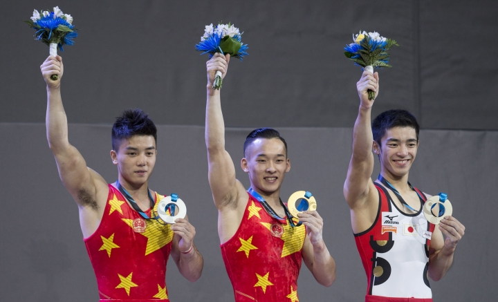 Men's individual all-around gold medalist, Ruoteng Xiao, center, of China, silver medalist Chaopan Lin, left, of China and bronze medalist Kenzo Shirai of Japan salute the crowd during medal ceremonies at the World Artistic Gymnastics Championships in Montreal on Thursday, Oct. 5, 2017. (Paul Chiasson/The Canadian Press via AP)
