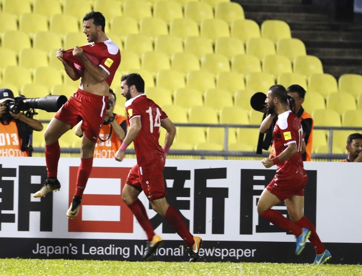 Syria's Firas Mohamad Alkhatib, left, celebrate after scoring goal during match against Australia during the 2018 World Cup qualifying football match between Syria and Australia at the Hang Jebat Stadium in Melaka, Malaysia, Thursday, Oct. 5, 2017. (AP Photo/Vincent Thian)