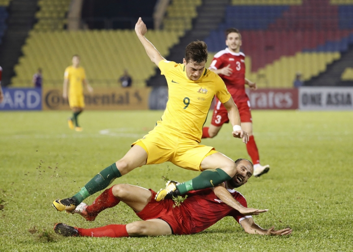 Australia's Tomi Juric, upper, fight for control of the ball with Syria's Hadi Almasri during the 2018 World Cup qualifying football match between Syria and Australia at the Hang Jebat Stadium in Melaka, Malaysia, Thursday, Oct. 5, 2017. (AP Photo/Vincent Thian)