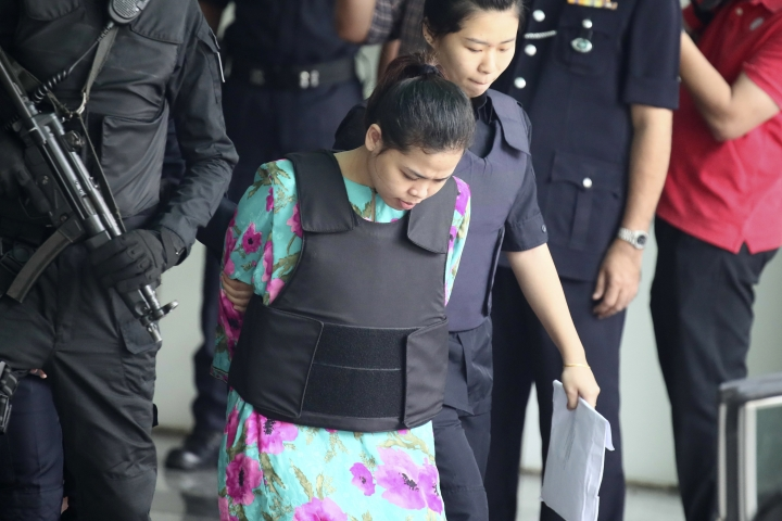 Indonesian Siti Aisyah, center, is escorted by police as she leaves a laboratory in Petaling Jaya, Malaysia, Monday, Oct. 9, 2017. The Malaysian court holding the trial of two women accused of killing the estranged half brother of North Korea's leader moved temporarily Monday to a high-security laboratory to view evidence contaminated with VX nerve agent. (AP Photo/Sadiq Asyraf)