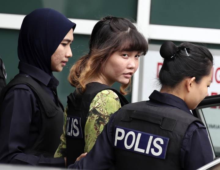 CORRECTS VERB - Vietnamese Doan Thi Huong, center, is escorted by police as she leaves a laboratory in Petaling Jaya, Malaysia, Monday, Oct. 9, 2017. The Malaysian court holding the trial of two women accused of killing the estranged half brother of North Korea's leader moved temporarily Monday to the high-security laboratory to view evidence contaminated with VX nerve agent. (AP Photo/Sadiq Asyraf)