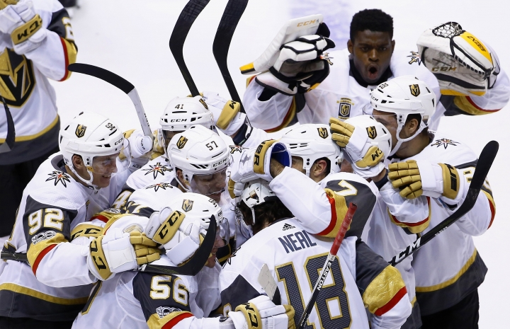 Vegas Golden Knights left wing James Neal (18) celebrates his game-winning goal against the Arizona Coyotes with Golden Knights left wing Tomas Nosek (92), left wing David Perron (57), left wing Erik Haula (56), left wing Pierre-Edouard Bellemare (41), and others during overtime of an NHL hockey game Saturday, Oct. 7, 2017, in Glendale, Ariz. The Golden Knights defeated the Coyotes 2-1. (AP Photo/Ross D. Franklin)