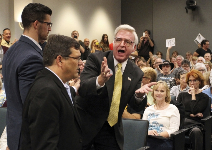 "In this Feb. 11. 2017 photo, Bill Akins, right, speaks during a Pasco Planning Commission hearing in New Port Richey, Fla. Akins was the first to file a patent for an attachment to a semiautomatic rifle that would enable it to fire bullets at a rate approximating that of an automatic weapon. Authorities said the Las Vegas shooter had a dozen similar devices, known as ""bump stocks,"" in his hotel room. (Brendan Fitterer/Tampa Bay Times via AP)"