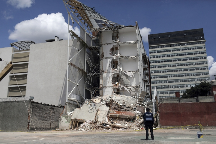 In this Sept. 24, 2017 photo, a police officer stands guard at an apartment building that was partially destroyed during the 7.1-magnitude earthquake, on Emiliano Zapata Avenue in Mexico City. The eco-friendly apartment building with its wood-paneled balconies and a solar-paneled roof collapsed when a corner column failed, and the flat-slab structure pancaked, said Eduardo Miranda, a professor of civil and environmental engineering at Stanford and global expert on earthquake-resistant design. (AP Photo/Miguel Tovar)