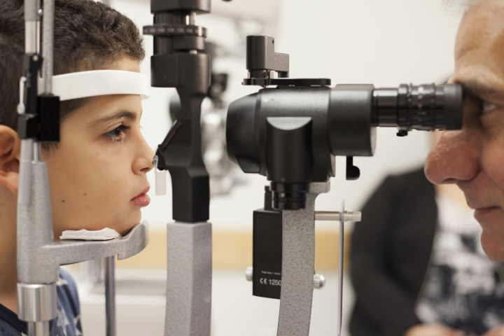 In this Oct. 4, 2017 photo, Dr. Albert Maguire checks the eyes of Misa Kaabali, 8, at the Children's Hospital of Philadelphia. Misa was 4 years old when he received his gene therapy treatment. On Thursday, Oct. 12, U.S. Food and Drug Administration advisers will consider whether to recommend approval of the gene therapy.(AP Photo/Bill West)