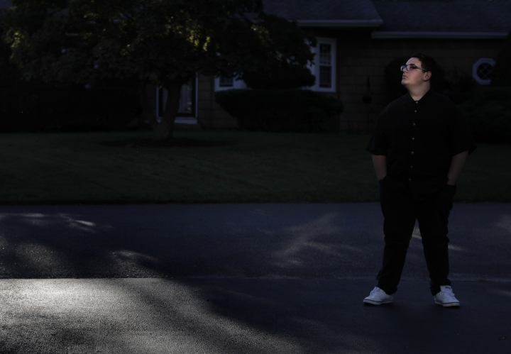 "In this Monday, Oct. 2, 2017, photo, sunlight reflected off a window lights up Christian Guardino's face, as he stands for a portrait outside his home in Patchogue, N.Y. Christian was diagnosed with hereditary blindness and received gene therapy as part of a study. On Thursday, Oct. 12, U.S. Food and Drug Administration advisers will consider whether to recommend approval of the gene therapy. Before treatment, ""It was dark, life without light,"" Christian said. ""I found a way to work through it, to cope with it, and that was music."" (AP Photo/Julie Jacobson)"