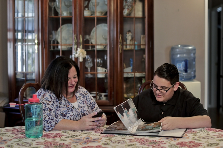 In this Monday, Oct. 2, 2017, photo, Beth Guardino, left, and her son, Christian, look through old family photos during an interview at their home in Patchogue, N.Y. Christian was diagnosed with hereditary blindness and received gene therapy as part of a study. On Thursday, Oct. 12, U.S. Food and Drug Administration advisers will consider whether to recommend approval of the gene therapy. (AP Photo/Julie Jacobson)