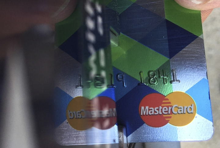 FILE - In this June 15, 2017, file photo, a customer inserts a credit card to pay for parking in Haverhill, Mass. A new credit card can offer richer rewards and a higher credit limit. But before applying, make sure it's really time to upgrade. (AP Photo/Elise Amendola, File)