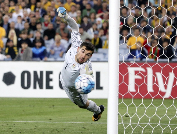 Australia's keeper Mathew Ryan dives at a ball that hit the post from a Syria free kick during their Soccer World Cup qualifying match in Sydney, Australia, Tuesday, Oct. 10, 2017. (AP Photo/Rick Rycroft)