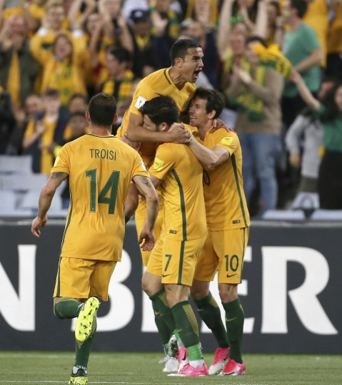 Australia's Tim Cahill, tops, celebrates with teammates after scoring against Syria during their Soccer World Cup qualifying match in Sydney, Australia, Tuesday, Oct. 10, 2017. (AP Photo/Rick Rycroft)