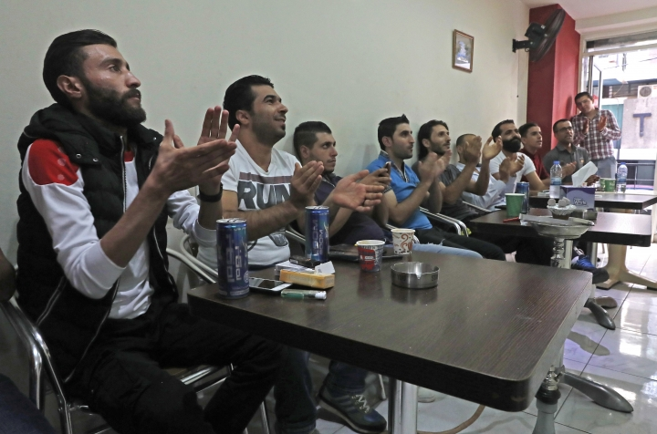Syrian soccer fans who live in Lebanon, applaud while watching the Soccer World Cup qualifying match between Syria and Australia, at a coffee shop in Beirut, Lebanon, Tuesday, Oct. 10, 2017. Taking a break from the raging war, millions of Syrians at home and abroad cheered, shouted and bit their nails in frustration as they watched their chance to qualify for their first ever World Cup tournament end in disappointment Tuesday. (AP Photo/Hussein Malla)
