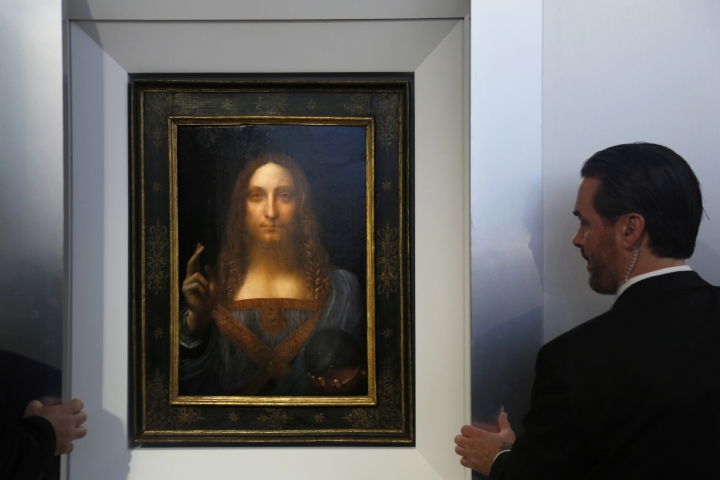 """Security guards open a door to reveal """"Salvator Mundi"""" by Leonardo da Vinci during a news conference at Christie's in New York, Tuesday, Oct. 10, 2017. The piece, which was painted around 1500, is one of fewer than twenty da Vinci paintings known to exist. After public exhibitions around the world, the auction is scheduled to take place on Nov. 15, 2017. (AP Photo/Seth Wenig)"""