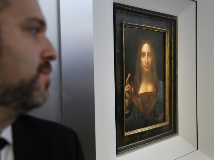 """A security guards stands near """"Salvator Mundi"""" by Leonardo da Vinci during a news conference at Christie's in New York, Tuesday, Oct. 10, 2017. The piece, which was painted around 1500, is one of fewer than twenty da Vinci paintings known to exist. After public exhibitions around the world, the auction is scheduled to take place on Nov. 15, 2017. (AP Photo/Seth Wenig)"""