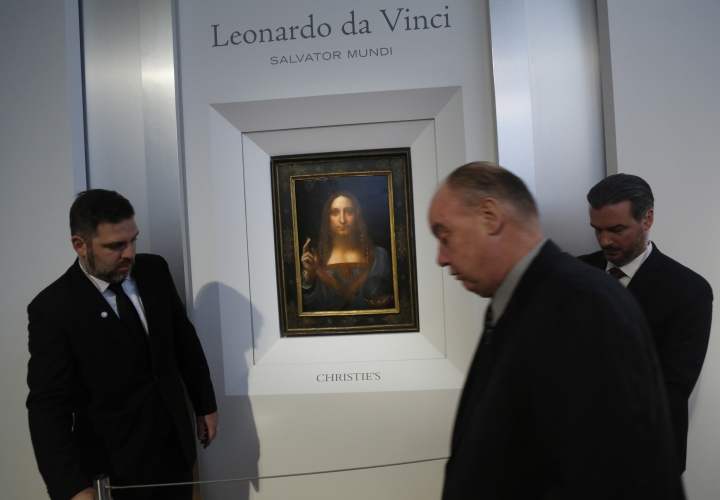 """Security guards set up a rope in front of """"Salvator Mundi"""" by Leonardo da Vinci during a news conference at Christie's in New York, Tuesday, Oct. 10, 2017. The piece, which was painted around 1500, is one of fewer than twenty da Vinci paintings known to exist. After public exhibitions around the world, the auction is scheduled to take place on Nov. 15, 2017. (AP Photo/Seth Wenig)"""