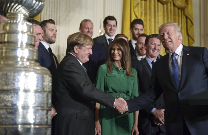 President Donald Trump, right, shakes hands with Pittsburgh Penguins owner Ronald Burkle, third from left, as first lady Melania Trump, center in green, watches, with Mario Lemieux during a ceremony to honor the 2017 NHL Stanley Cup Champion Pittsburgh Penguins, Tuesday, Oct. 10, 2017, in the East Room of the White House in Washington. (AP Photo/Susan Walsh)